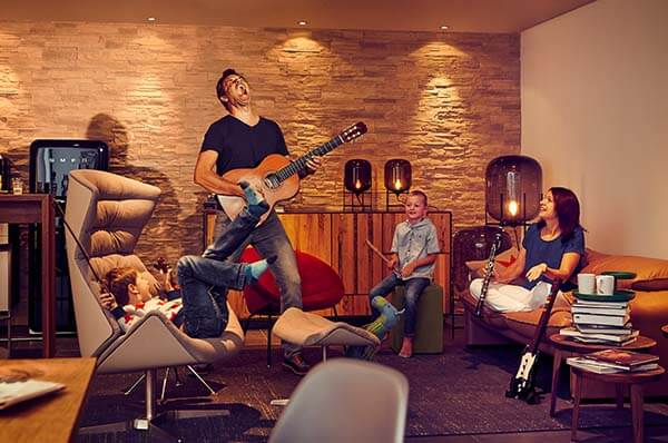 Junge Familie im Wohnzimmer, Vater mit Gitarre, Spaß, Da flipp ich aus